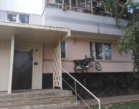 Пенсионер хранит мотоцикл под балконом